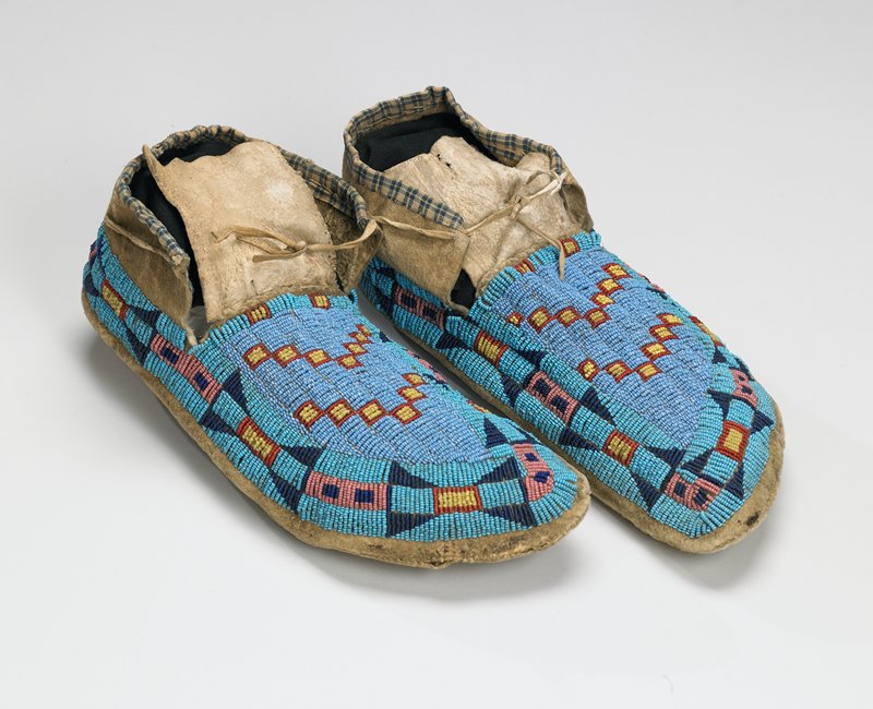 rawhide soles; tanned uppers; geometric beaded designs over top in blues, red, pink and yellow; blue plaid cloth around ankles