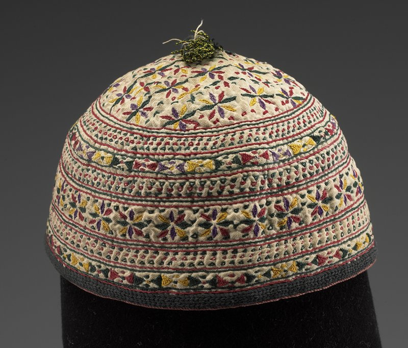 beanie shape with multicolored embroidered horizontal bands of geometric shapes and flowers; circular floral area at top; tassel at top