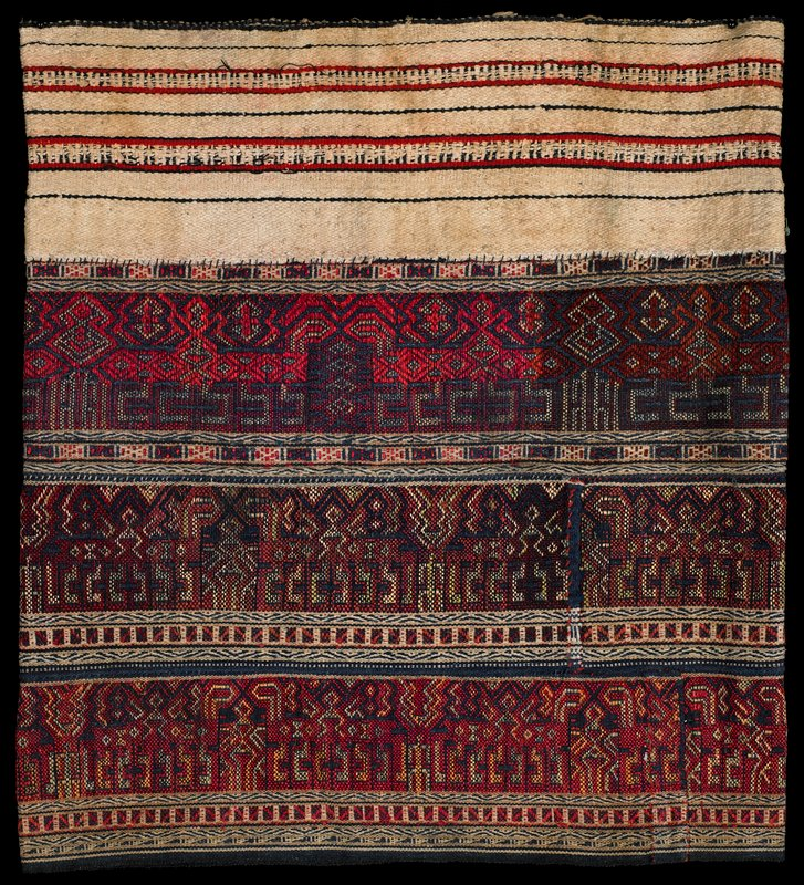 four horizontal strips; top band is off-white with red and blue stripes (small inset of white with blue and light tan striped fabric); lower three bands are predominately red and dark blue, woven with geometricized animals and geometric bands