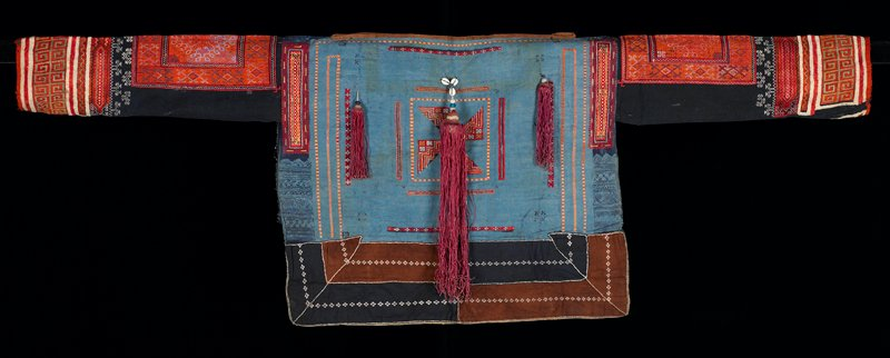 pullover shirt with wide boat neck; open ides; blue batik body; dark indigo long sleeves; cross stitch embroidery in primarily orange--geometric patterns; three tassels on back--rose-colored, trimmed with large beads and cowrie shells; brown trim at neck; brown and blue tail on back