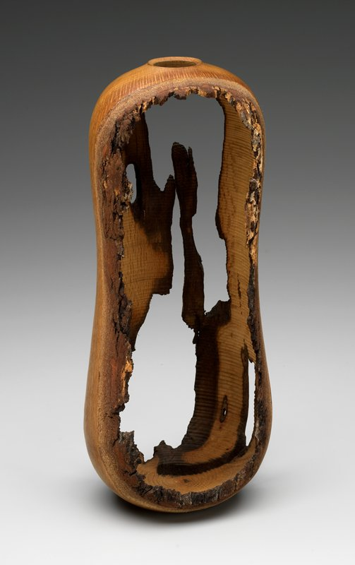 tall gourd-shaped vessel with large, irregular openings; small mouth at top