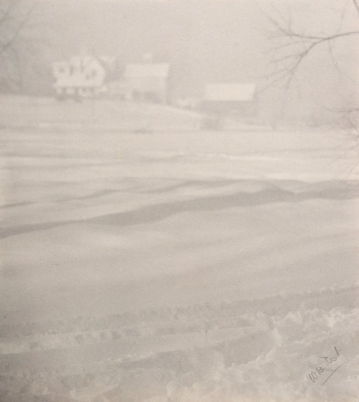 snow with tracks in foreground; large house and barn in distance