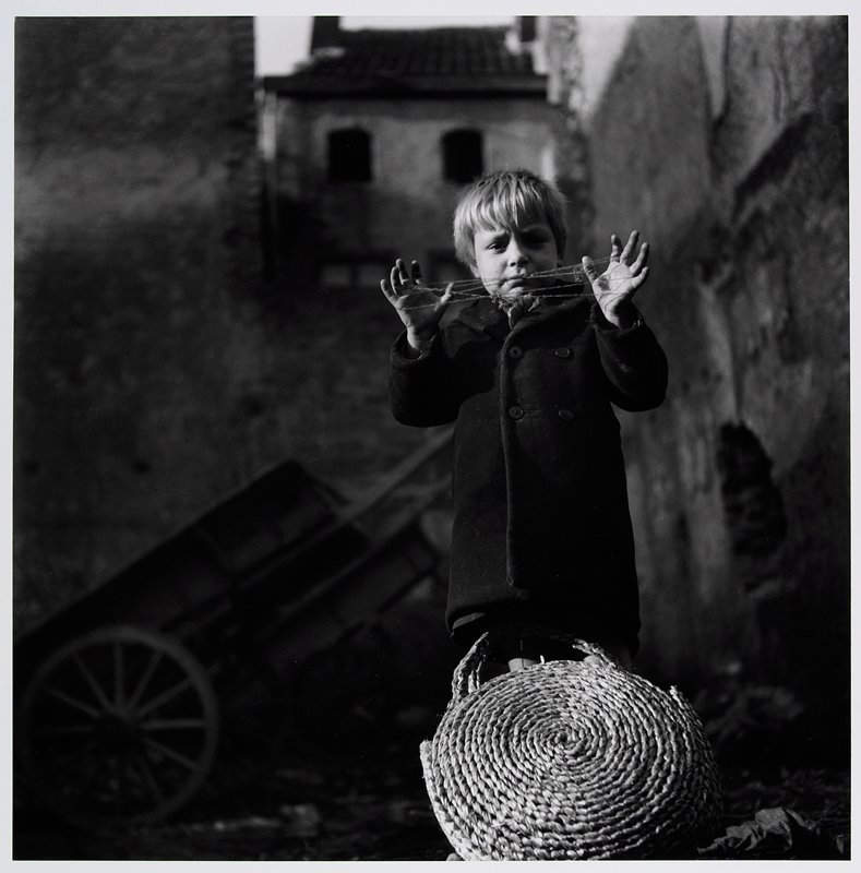 standing child wearing an overcoat, with a round straw bag at feet, playing cat's cradle with a string