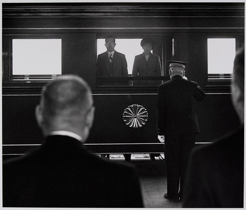 standing couple behind a window with a metallic flower medallion below it; back of man wearing a cap and white gloves visible in middle ground; back of 2 men's heads in foreground