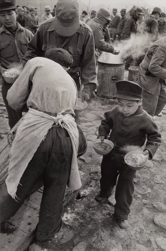boy holding 2 bowls of food; lines of soldiers being served food from steaming garbage cans
