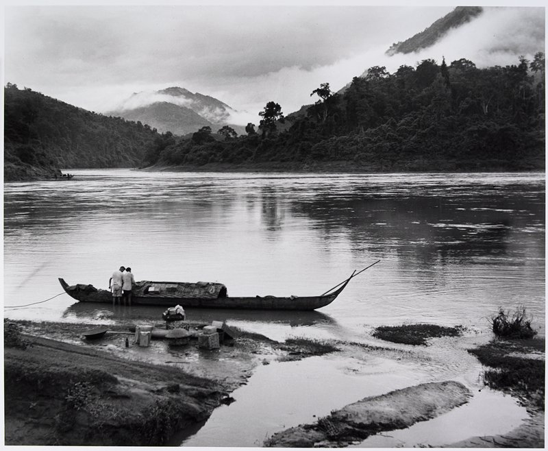 2 men adjusting cover on a long sailboat; parcels on the shore; tree-covered mountains, with tall peaks covered in mist, on opposite riverbank