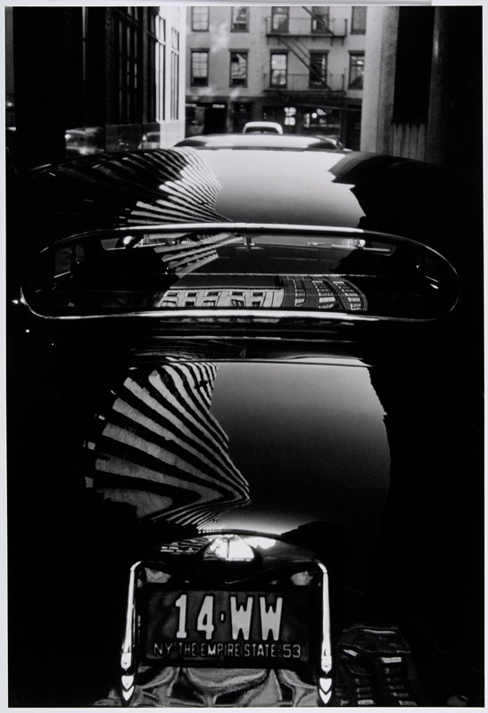 reflections of buildings on trunk, top and back window of shiny, dark car
