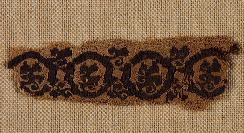small band fragment decorated with organic repeating design; dark brown on tan