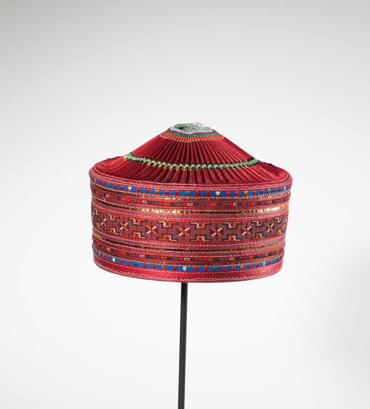 vertical sides; slightly conical crown with opening at top; red with metallic strips; three embroidered strips on front with geometric patterns