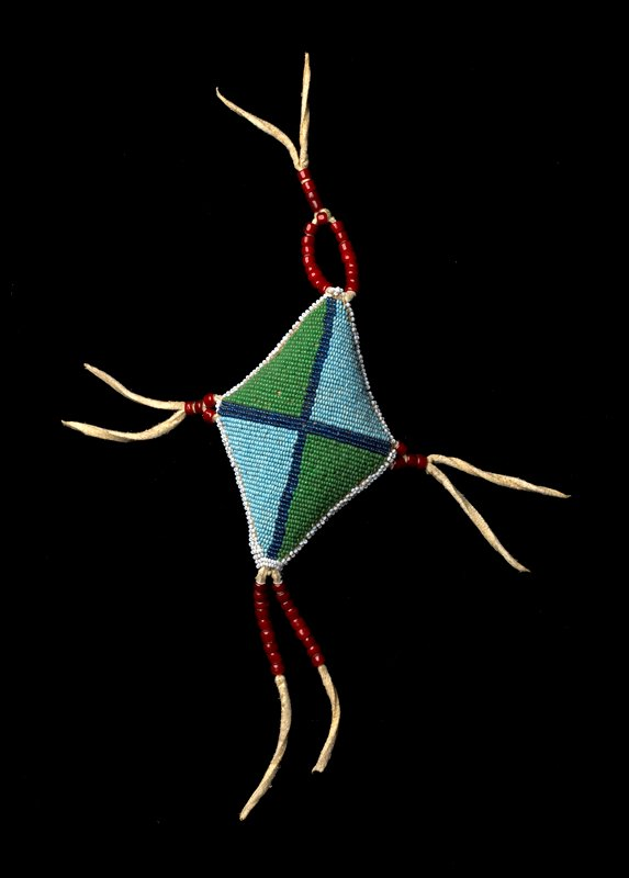 diamond shaped stuffed amulet, beaded overall in simple linear design in red, green, white, clear, light blue, dark blue and green beads; tassels at corners decorated with red beads