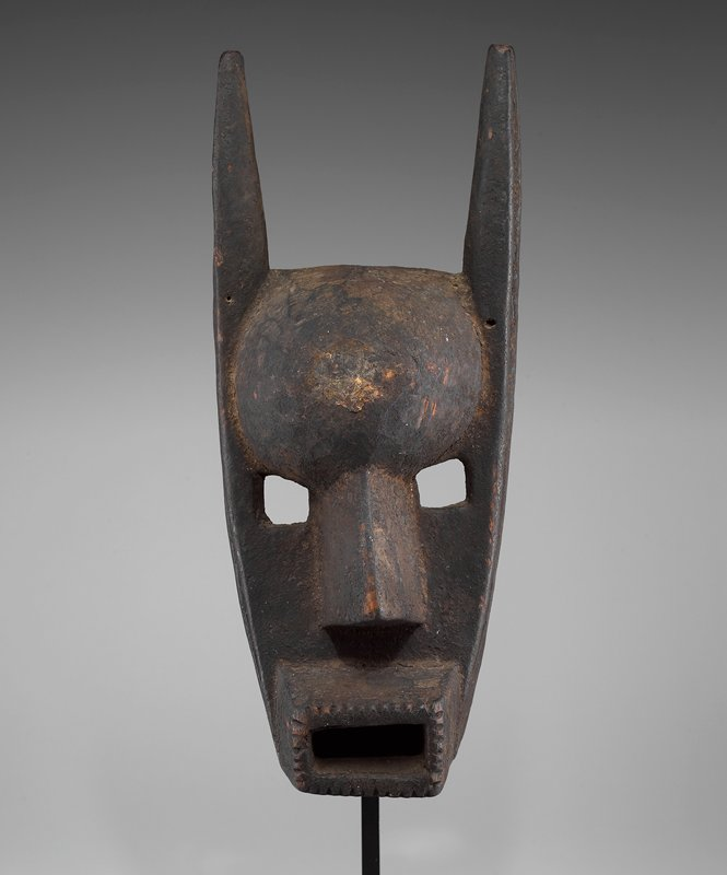 long, thin face with open rectangular mouth; 4-sided eyes; human nose; vertical horns; dark patina