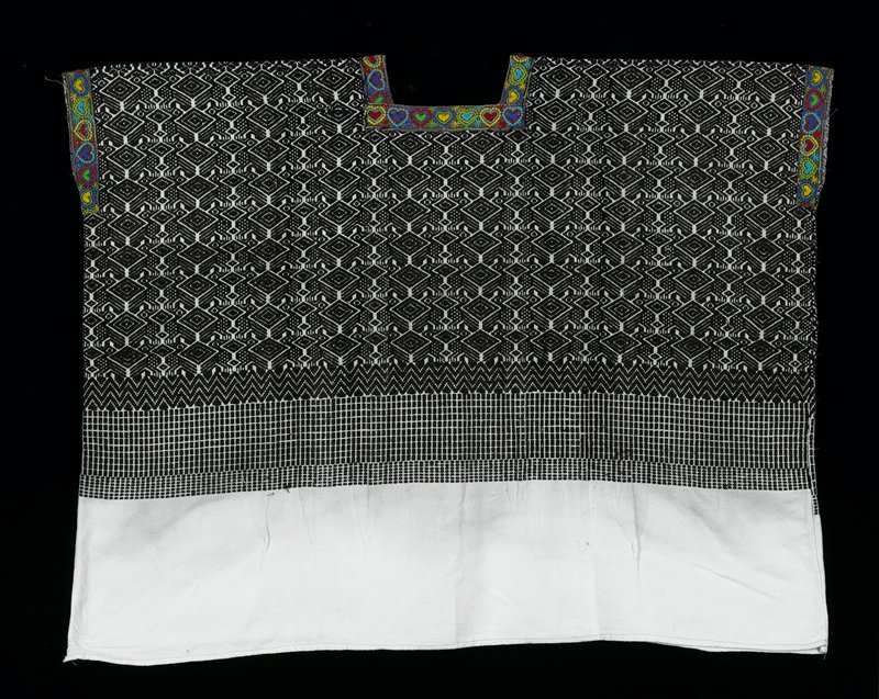 One panel huipil with square-cut neck opening; white ground cloth with black geometric brocade patterns; neckline and armholes have an applied embroidered.