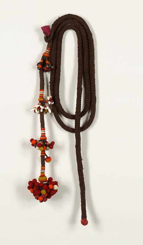 Brown braided sash with tassles made of small red, orange, green, white, blue balls knitted over insect shells, shells.