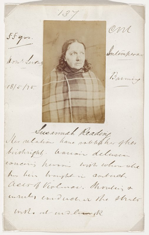 portrait of a woman with a round face, large eyes and shoulder-length hair, with a plaid blanket wrapped around her body; photo glued to folded paper with various pen inscriptions