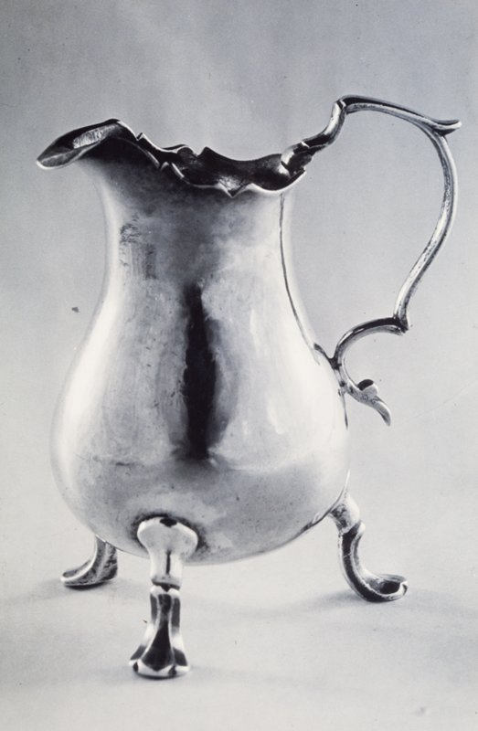 cream jug, pear-shaped, with shaped rim and folded lip; on three double-scrolled legs with flat, three-lobed feet; shaped scroll handle
