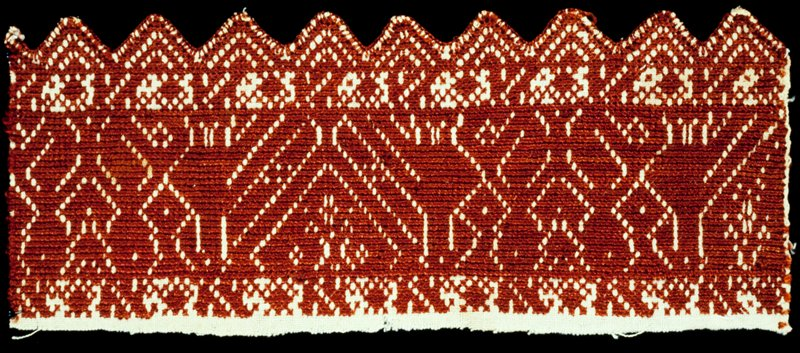A band of linen embroidered with dark red silk in ornaments and birds facing each other. Lower edge pointed.