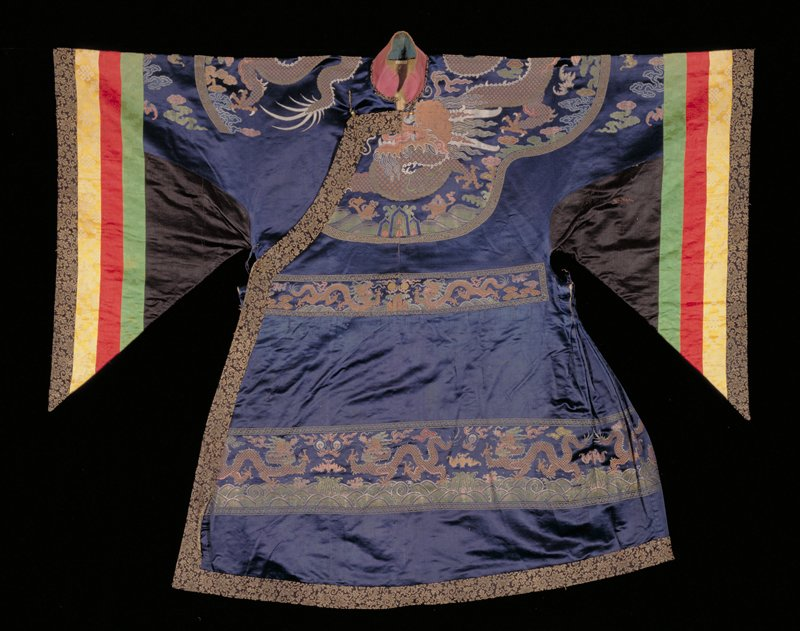 (Initially a 'ch'ao-fu' court robe; altered in Tibet for ritual Lamaist dances, large triangular panels and striped cuffs were added to the original tapered sleeves.) Court Robe of dark blue satin; in upper section, back and front, a shaped panel extending over shoulders with large four-clawed dragon in gold; clouds, bats, and Eternal Sea motif in shades of blue, green, yellow, rose and rust; at back and front waistline, where skirt of robe is seamed to upper section, a band of dragons and clouds in gold and colors; a wider band of the same borders the skirt all around ten inches from the bottom; collar band and border of gold and black floral brocade; standing collar of fuschia cotton; large wing-like sleeves made of black satin and strips of green, yellow and crimson satin brocade with an outer border of the black and gold floral brocade; canvas lining; note tailoring of this robe, with the wide skirt caught into stiff pleats over the hips, and the long, triangular sleeves; A.P.( Alfred Pillsbury) thinks a court robe remodelled for Lama Dances