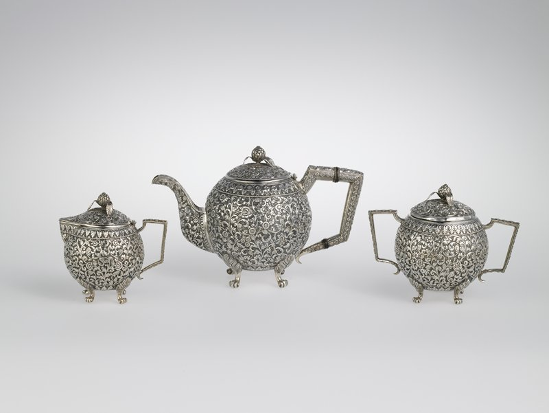 spherical body; hinged lid with organic finial with three raised leaves; four scrolling feet; overall decorations (body, cover, handle and spout) of relief floral designs