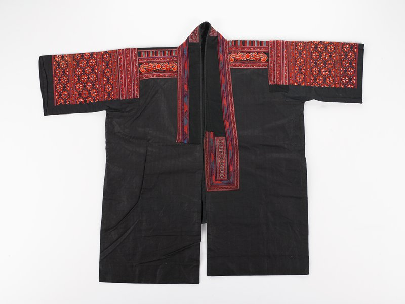 dark blue overall; predominately red embroidery on tops of sleeves, around front opening and on collar; applique on collar; geometric and floral shapes, with four fantastic animals on shoulders