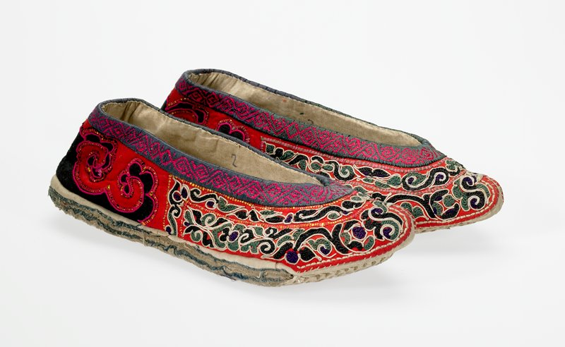 pointed toes; black and red embroidered and appliqued upper with scrolling leaf-like designs, edged in white; green and pink, and blue and pink, edging at opening