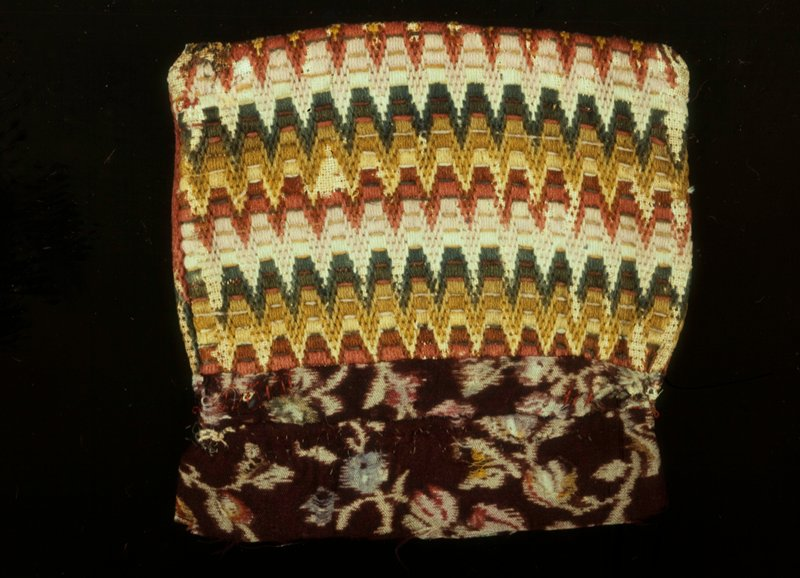 Bag, each side of which is of different design; one side conventionalized repeat design of various shades of red, green and white. Other side has different design consisting of concentric lozenges. Whole bag embroidered on canvas with worsted.