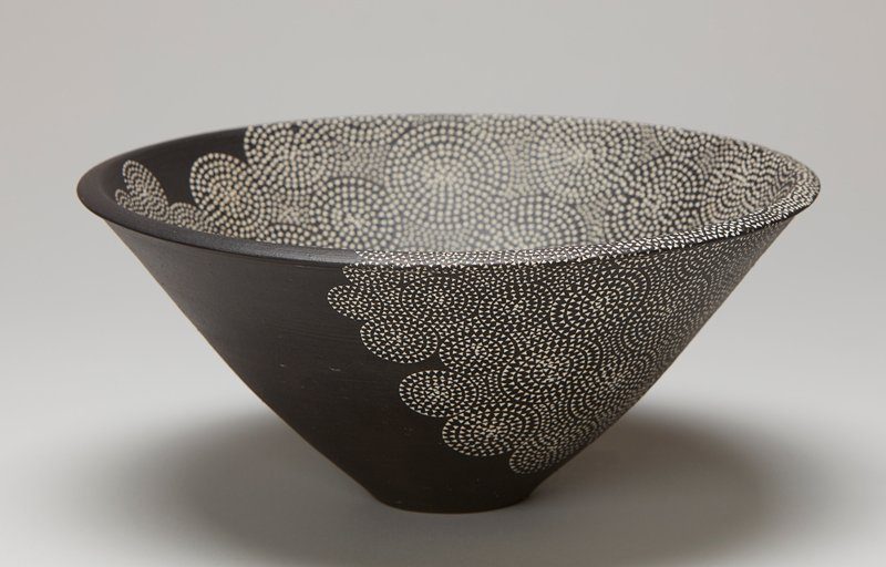 black bowl with incised tiny white triangles; triangles form circles; wide at top and narrows significantly at foot