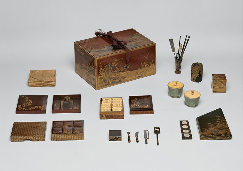 outer storage box for incense game set; box features gold and silver designs of a landscape with tree and bird, scholar's rock, and blossoming trees with stylized waves; contains other sets of smaller boxes inside, containing game pieces and incense storage containers, each decorated in gold with motifs from nature and of small buildings on stilts; many separate tools including a tamper, tongs, chopsticks, and cutting tools; two ceramic incense bowls; square multi-layered gold box with similar decorative motifs, writing box, and a box containing incised ivory chips