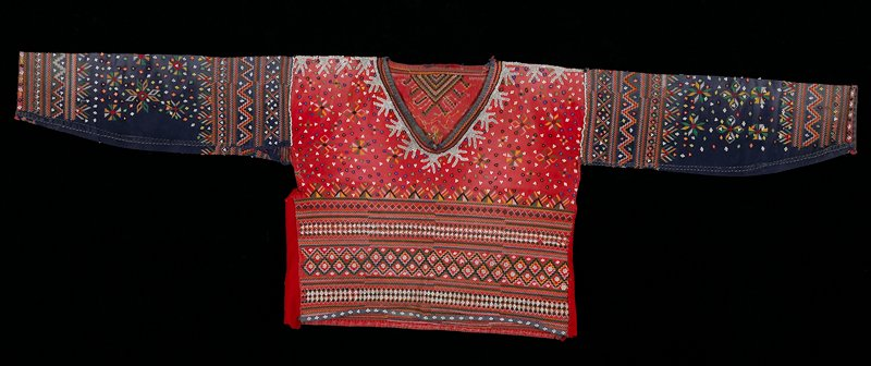 Red body with cross stitch in green, yellow, black, and white; beads; blue sleeves with multicoulored cross stitch pattern and beads; front and back decorated.