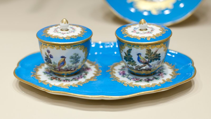 condiment dish; tray fitted with two fixed pots and covers; blue turquoise surface; the pots each have two panels reserved in white, wreathed in gold and painted with birds in branches; lids of pots each have a panel reserved in white, wreathed in gold and carrying a floral wreath; the shaped tray carries similarly decorated panels at the base of the pots; the panels all painted by Falot; stone grey underglaze