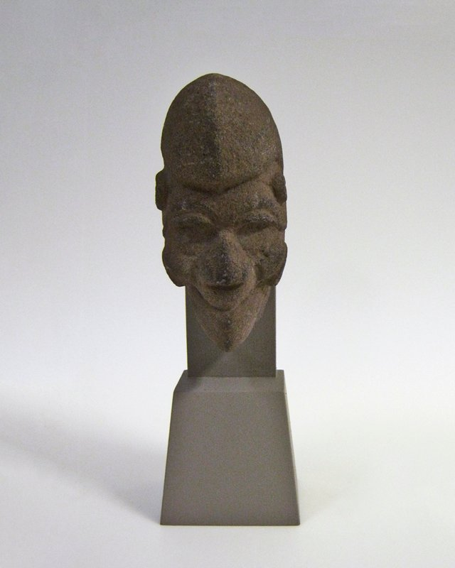 Head, architectural in character, of the type known as 'Hacha'. Sharply-cut features with large nose, deep-cut eyes, and lipless mouth turned up in a grin. Large scroll forms in relief at temples and on cheek. Cap-like headdress comes forward over the brow in a large puff.