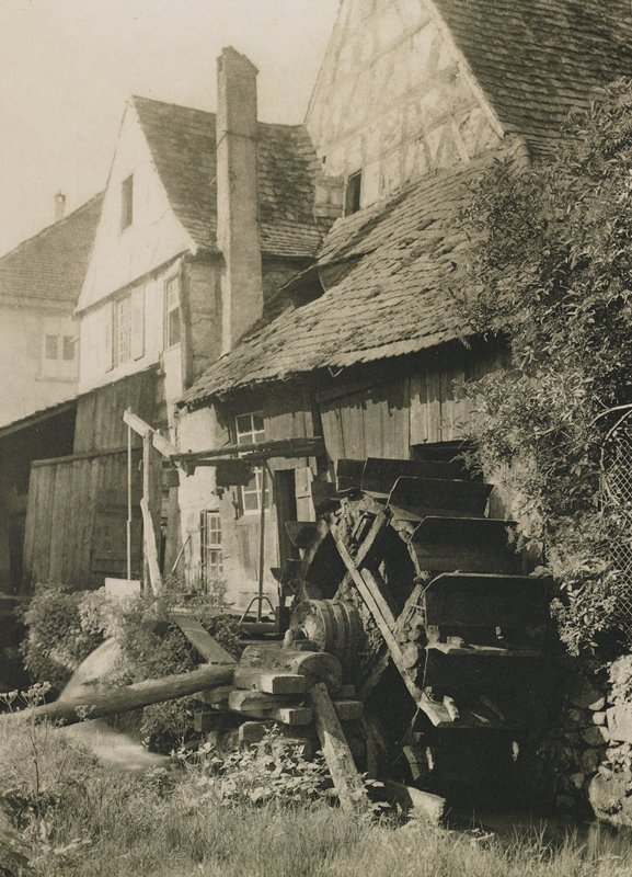 water mill wheel attached to old buildings; trees at R