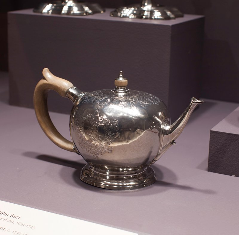teapot, globular body on moulded flaring base; on the shoulders an engraved band of scrolls and latticed panels; on one side a coat-of-arms, unidentified