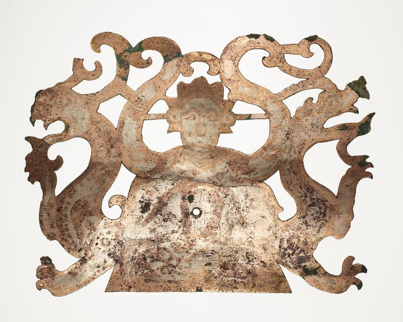 openwork plaque with bell-shaped bottom; human head at top center; upper bodies of fantastic animals at R and L; incised details; mounted on black cloth-covered board