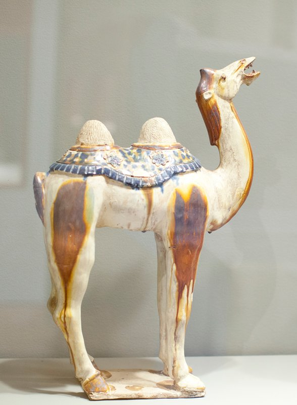 Camel, Bactrian type, with saddle blanket with Sassanian decoration. ca. 725 A.D. Glazed pottery tomb figure, one of a pair, on a flat base. Glaze predominately brown and yellow with mottlings of blue, green, and yellow.