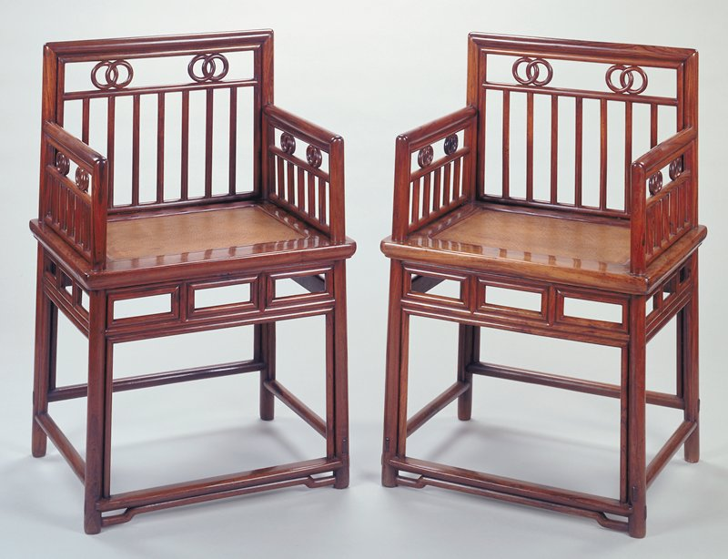 chair with arms and straight back; seat of woven natural fibers; each arm and back decorated with straight spindles and two pairs of interlocked rings