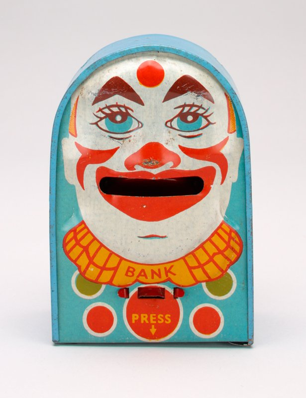 light blue rectangular box with round roof; face of clown on front side; clown has pointed triangular eyebrows and a red dot between them; front and back have red, yellow and green circles with rings around them