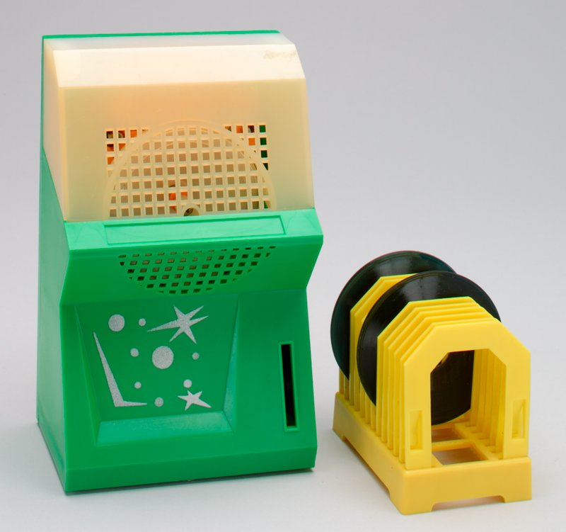 a: juke box; plastic; green, yellow and white; coin slot in front; sound grill in plastic; b: record holder; yellow plastic rack; c: record #35; black, green label; d: record #36; blue label; e: record #37; red label; coins in bank; battery operated