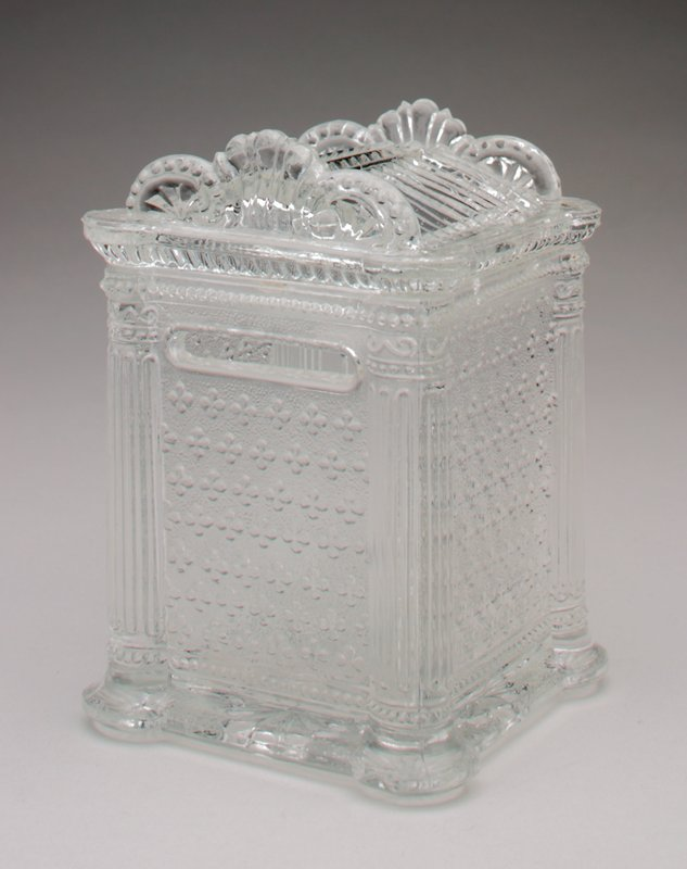 clear glass; moulded in the shape of an elaborate safe; coin slot on back at top