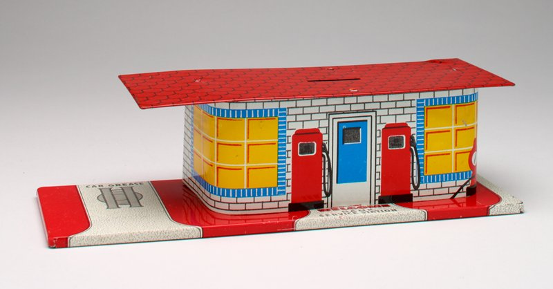 "tin printed in service station design; 2 gas pumps and air hose on front; ""WASHING"" and ""BATTERY"" over black doorways on back; red tile roof; key taped on bottom"