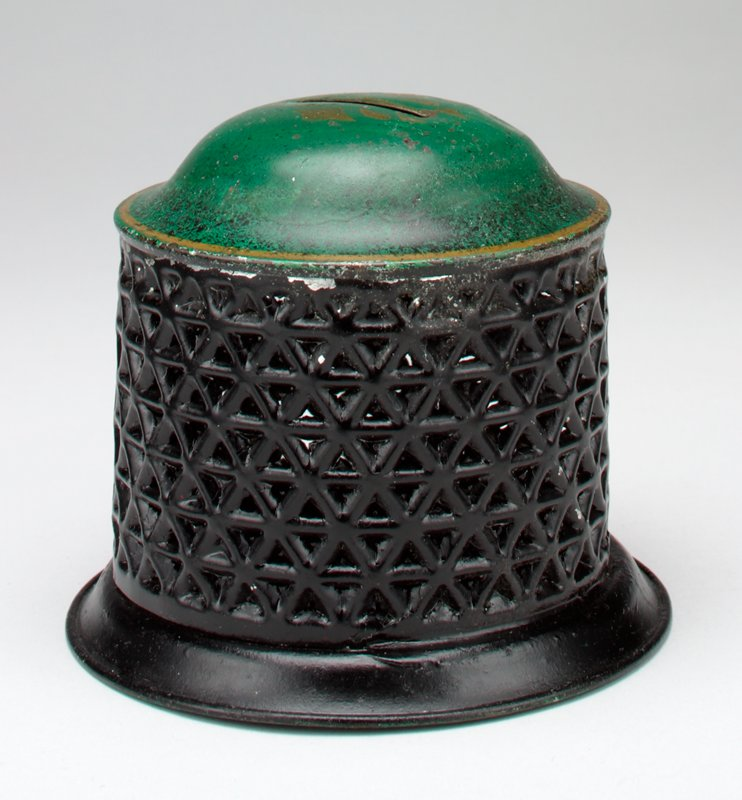 cylindrical openwork body, black; black base; domed green cover with gold trim and designs