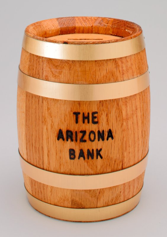 "bank shaped as a barrel with brass bands; slit on top; ""THE ARIZONA BANK"" printed on front; plastic combination key on bottom"