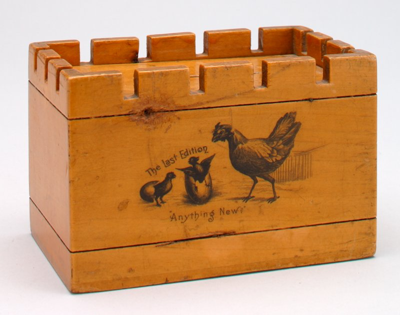 rectangular wooden bank with crenulated top; black transfer print of chicken and chicks coming out of eggs; swing-up top with slot; black groove around total rectangle top and bottom