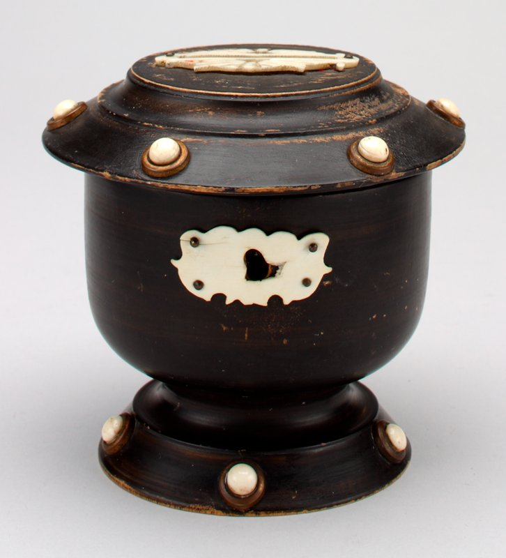 wood urn-shaped bank with hinged cover painted black; brass lock and keyhole; ivory decor around keyhole and coin slot; ivory beads surrounded by brass rings encircle the cover and the foot