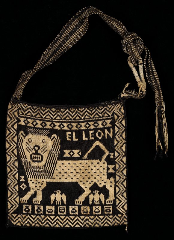Knitted bag in off-white and black with lion design on one side and horse designs on the other side; strap knotted to a ring made of wood