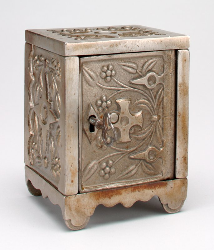 "solid steel sides, each with a central star and floral motifs in relief; has a key; on bottom: ""Key Lock Safe No. 50"""