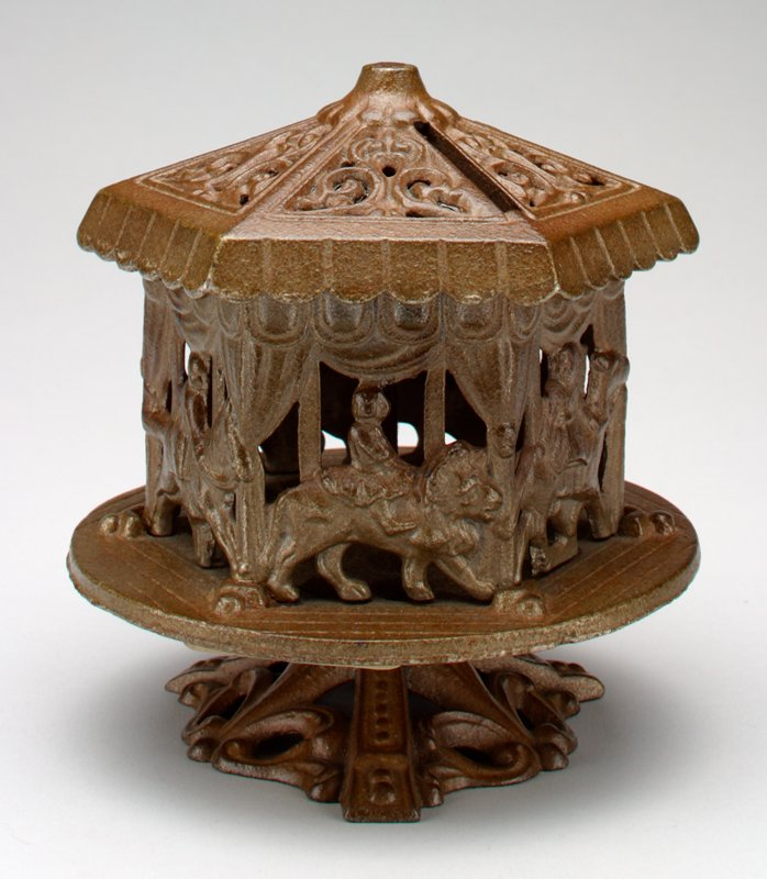 merry-go-round atop 3-legged base on which it rotates; round imited wood planked base; 6-sided with children riding horses and lions; scrollwork at top with coin slot