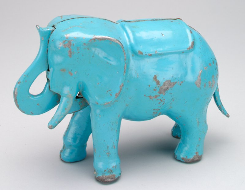 light blue standing elephant with trunk to forehead; press tail in, trunk moves forward to deposit coin in forehead; screw fastens sildes together at PR side; blanket draped over back of elephant