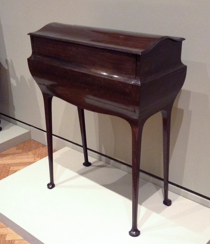 small console of dark wood exterior; thin four-sided legs on splaying feet; top opens and front unfolds forward to writing surface; eight drawers and two cubbyholes