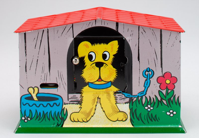 aluminum folded bank in the shape of a dog house; red slanted roof with shingles; green slanted foot; kitten, 2 puppies in a basket, duck and chicken with butterfly wrap around exterior; at front a dog is lying; knob at front opens the dog's mouth, sticking out a red disc to accept coins; trigger at left front closes mouth and takes coin; key taped to underside