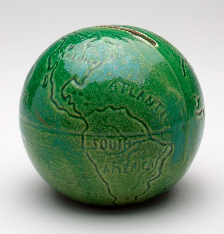 green ceramic world globe with shiny glaze; continents and oceans are labeled; slot on top